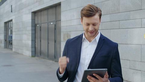 Businessman using digital tablet at street. Worker celebrating victory outside Live Action