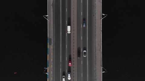 Bridge highway dark water cars traffic aerial top view tracking shot Live Action