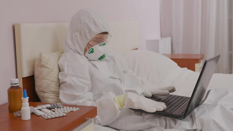 A boy in a protective suit and a respirator at home at a computer isolated Live Action