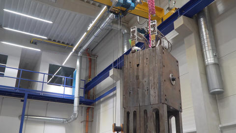 crane in a factory relocating heavy metal objects between production lines Live Action