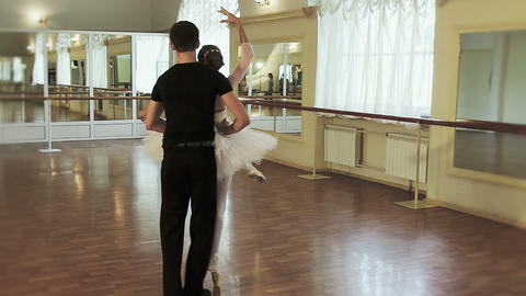 Young man spins woman around, couple practicing ballet in studio Footage