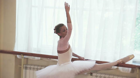 Senior ballerina exercises at the barre in studio, slow motion Footage
