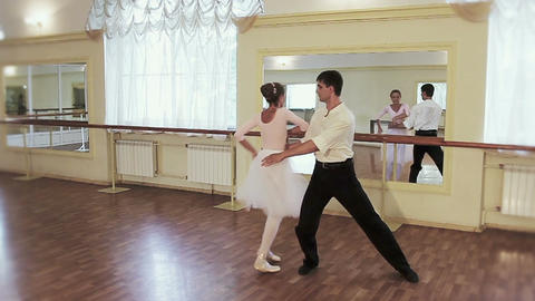 Young man dancing classical ballet with elderly woman in gym Footage