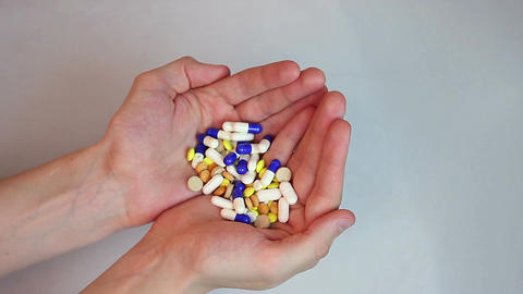 Person holding two handfuls of colorful tablets and capsules Footage