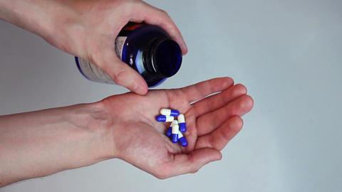 Hands pouring out blue capsules out of the medicine bottle Footage