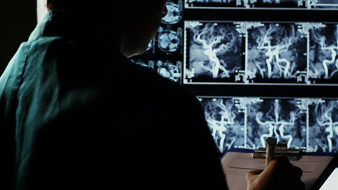 Doctor studying X-ray images human body, writing down diagnosis Footage