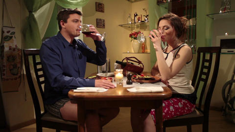 Funny young couple in pajamas having romantic dinner at home Footage