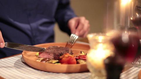 Handsome male enjoying freshly grilled steak in restaurant Footage