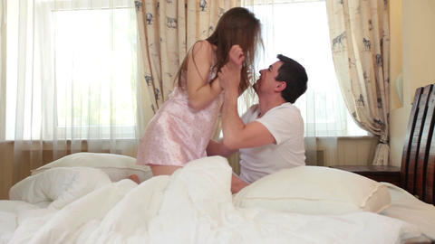 Young couple playfully wrestling in bed and then start kissing Footage