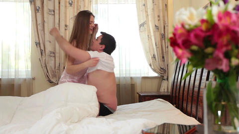 Sexy girl in lingerie undressing and kissing boyfriend in bed Footage