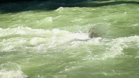 Wide mountain river flowing rapidly over the rocks, green water Footage