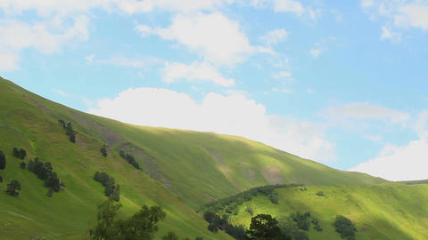 Cumulus clouds moving across blue sky, green hills, time-lapse Footage