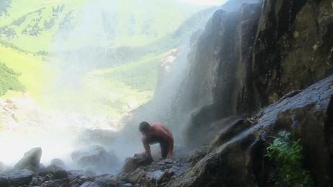Shirtless man walking under waterfall, water splashing around Footage