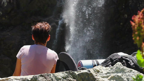 Woman tourist watching waterfall in mountains, running water Footage
