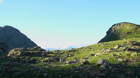 Green mountain slope, stream flowing between rocks, blue sky Footage