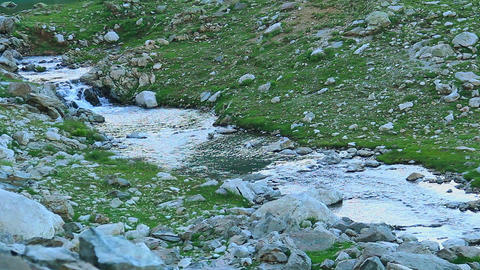 Peaceful mountain stream flowing over the rocks, green valley Footage