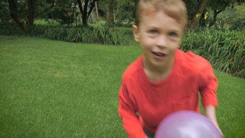 A young 5 year old boy in a red shirt with red blond hair plays outside with a b Footage