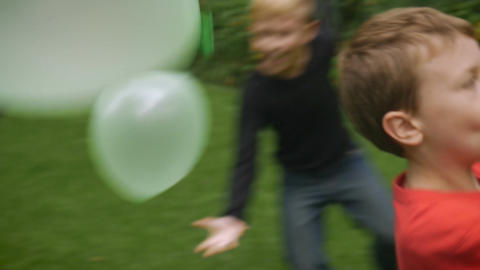 A couple of young boys play balloons outside in a park with their mother in slow Footage