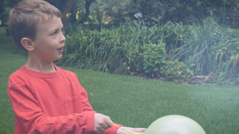 An adorable redhead boy playing outside with a balloon pauses to talk about some Footage