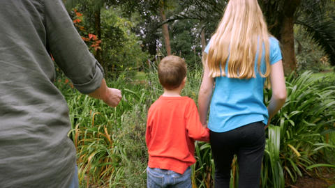 A mother and her kids stop to smell lavender growing in a park or a garden - slo Live Action