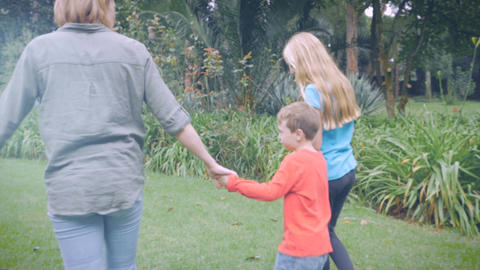The camera follows a little boy in a red shirt while holding hands with mother a Footage