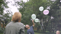 A family of five have a day in the park together playing with balloons and havin Footage