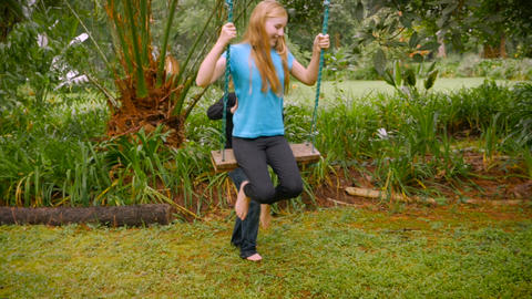 A little blond haired boy pushes a young girl on a swing in a park - slowmo Footage