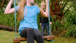 A young girl with blond hair on a swing kicks her legs back and forth while a bo Footage
