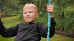 A blond boy having fun swinging on an old fashion swing - slowmo Footage