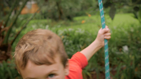 An adorable little boy swinging on a swing outside towards the camera - handheld Footage
