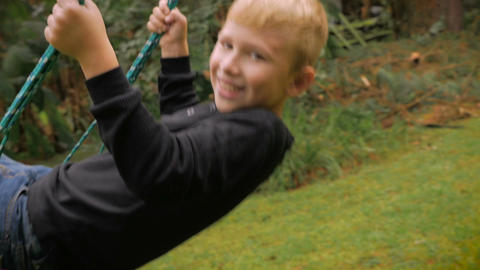A very adorable blond haired boy swinging on a swing while looking at the camera Footage