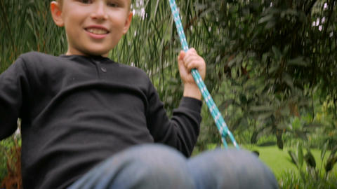 An all American blond boy swinging on a swing directly in front of the camera - Footage