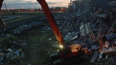 excavator operates at demolition of sports stadium at dusk Live Action