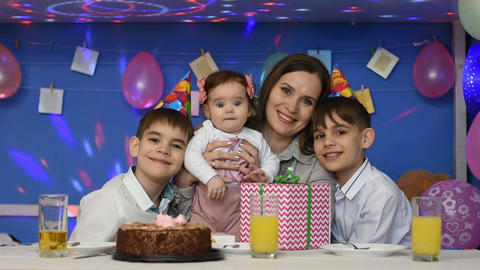 Cheerful family, mom, daughter and two boys at a family birthday party look at the frame Live Action