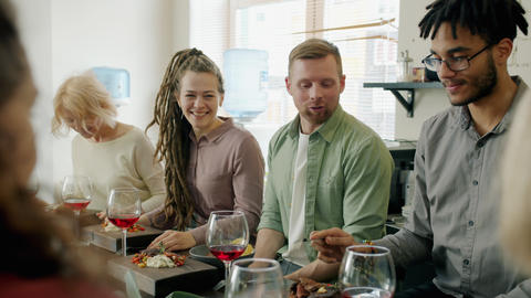 Diverse group of adults chatting and laughing sitting at table with food and Live Action