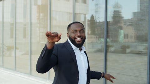 African businessman dancing in city. Business man celebrating success on street Live Action