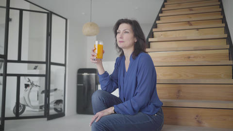 Portrait of attractive Caucasian woman sitting on stairs indoors and drinking Live Action