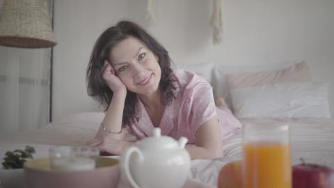 Positive brunette Caucasian woman in pink pajamas looking at camera and smiling Live Action