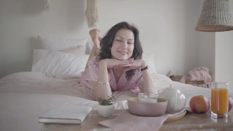 Portrait of gorgeous adult Caucasian woman lying on bed in the morning and Live Action