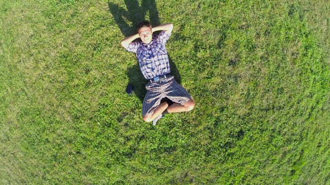 Happy man lying on grass hands behind head, aerial shot Footage