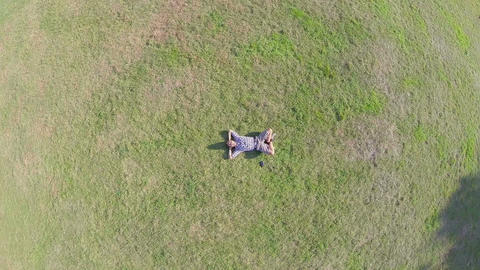 Aerial, young positive man lying on ground hands behind head Footage