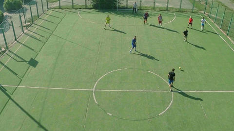 Group of young men playing soccer on pitch, sports aerial Footage
