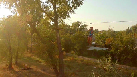 Female flying zipline high above the ground, active rest, sports Footage