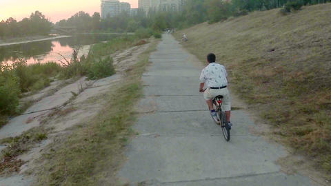 Man riding bicycle in park alley near river, aerial shot Footage