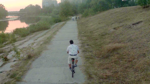 Young man cycling in park, panoramic view of city, aerial Footage