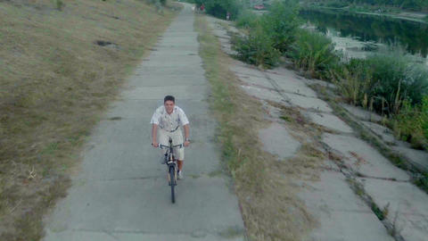 Young positive man riding bicycle fast on park alley, aerial Footage