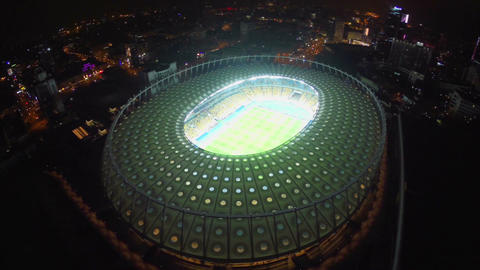 Flying over football stadium at night, city lights, panorama Footage