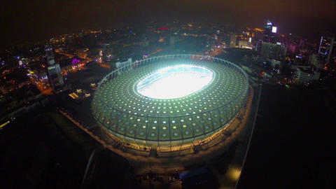 Aerial of large illuminated stadium at night, city landmark Footage