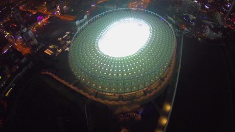 Flying high above the illuminated stadium, night city lights Footage