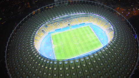 Flying over the top of large illuminated stadium, football match Footage
